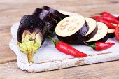 Chopped aubergines and chilly pepper on cutting board on wooden background