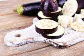 Chopped aubergines on cutting board on wooden background