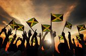 stock photo of jamaican  - Group of People Waving Flag of Jamaica in Back Lit - JPG