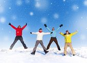 Group of young happy people jumping in snow and enjoying winter.
