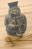 Asian Figurine And Two Chopsticks