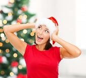 christmas, x-mas, winter, happiness concept - surprised woman in santa helper hat