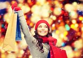 shopping, christmas sale and gifts concept - happy asian woman in winter clothes with shopping bags