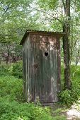 Old wooden outdoors toilet in summer.