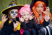 Portrait of three little girls in Halloween costumes looking at camera with frightening gesture