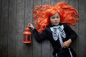 Portrait of cute girl in red wig and with lantern looking at camera