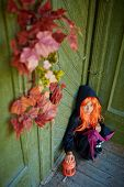 stock photo of traditional attire  - Halloween girl in traditional costume sitting on the porch of dilapidated house - JPG