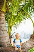 Baby sitting near palmtree on the beach