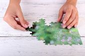 Hand holding puzzle piece on wooden table background
