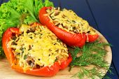 Stuffed red peppers with greens on wooden stand on table close up