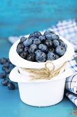 Tasty ripe blueberries in bowls, on wooden table
