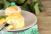 Tasty mini cakes with fresh peach, on wooden table