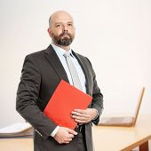 An image of a handsome business man with a red folder