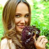 Beautiful slender girl holding healthy fresh greens, toned