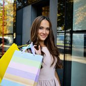 Beautiful young fashion woman holding shopping bags and standing near shop window, toned