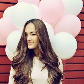 Happy young woman over red brick wall and holding pink and white balloons and gives a wink. Image toned.
