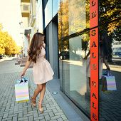 Beautiful young fashion woman with shopping bags looking at shop window