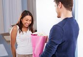 Man Giving Bouquet To Happy Woman