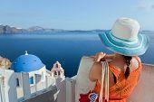 Happy woman in sun hat enjoying her holidays on Santorini island, Greece. View on Caldera and Aegean