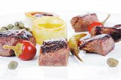 european food: grilled meat goulash on white plate with hot pepper, capers and sauces