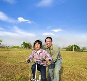 Happy Father Teaching His Daughter To Ride Bicycle