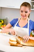 picture of fresh slice bread  - Young woman slicing fresh bread in kitchen - JPG