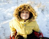 stock photo of toboggan  - little cute boy in hood with fur on snow outside - JPG
