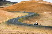Road with cars leading through the mountain landscape looks like a big symmetric S letter, Iceland.