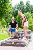 stock photo of miniature golf  - Couple playing together miniature golf - JPG