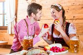 Couple having dinner at mountain hut in alps drinking beer and eating cold cuts