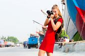 Woman photographing ships while sightseeing at harbour in Jakarta Sunda Kelapa