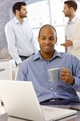 foto of black tea  - Closeup portrait of young black businessman sitting at desk - JPG