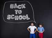 picture of frot  - Cute boy and girl standing in frot of a big blackboard - JPG