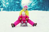 Mom With A Child Sledding And Having Fun In Winter Day