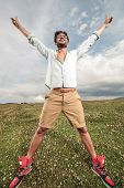 Young fashion man enjoying life and freedom outdoor on a field of grass. He is standing with both hands in the air, looking up and smiling.