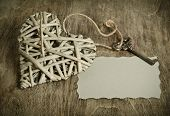 Wicker Heart Handmade With The Key Lying On A Wooden Base With A Sheet Of Paper