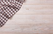 Top view of checkered tablecloth on white wooden table.