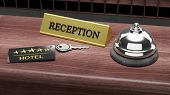 Hotel reception bell and and key on reception wooden desk