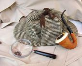 stock photo of sherlock  - A tweed hat like Sherlock Holmes wore along with a magnifying glass and calabath pipe on a trench coat - JPG