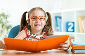 clever cute child girl wered eyeglasses with book