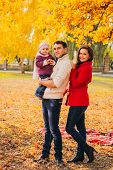Picture Of Lovely Family In Autumn Park, Young Parents With Nice Adorable Kids Playing Outdoors, Fiv