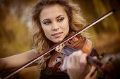 stock photo of violin  - Young woman playing the violin at park - JPG