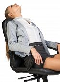 Businesswoman resting in office chair with her head thrown back