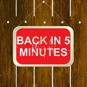 Back In 5 Minutes Sign Hanging On A Wooden Fence