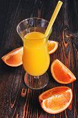orange juice with orange slices on a wooden background