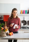 Portrait Of Concerned Young Housewife In Kitchen With Shopping B