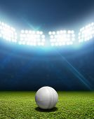 stock photo of illuminating  - A cricket stadium with a white leather cricket ball on an unmarked green grass pitch at night under illuminated floodlights - JPG