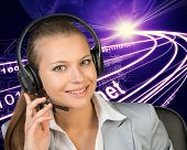Closeup of businesswoman in headset, wire-frame building with light as backfrop