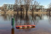 stock photo of groundwater  - public seat is under water in flood of river at springtime - JPG