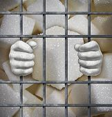 stock photo of ban  - Sugar ban concept as cubes of sweet white granules behind bars in jail as a symbol for the health risk of sweeteners in our diet - JPG